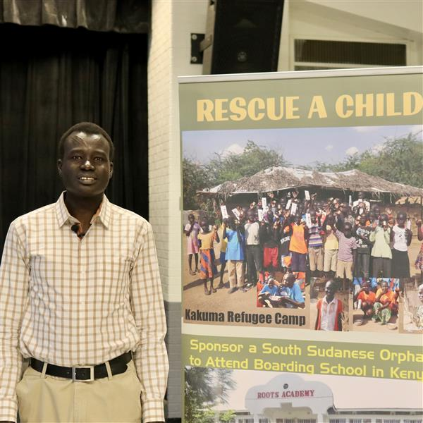 custodian Arok Garang next to a picture of his charity