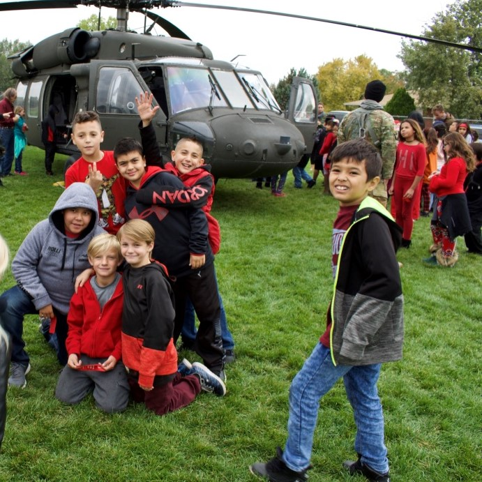 students pose with a black hawk helicopter