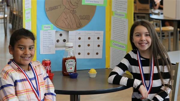 tow girls smiling next to science fair project