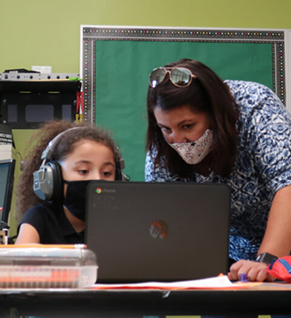 Hodgkins teacher with student working on her Chromebook