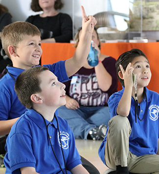 Three boy students raise their hand for a question at the Denver Museum.