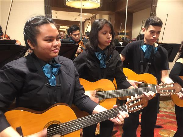 three students playing the guitar in the student mariachi band