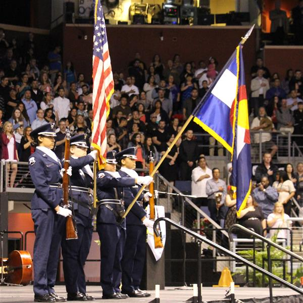4 students in the AFJROTC program hold up a colorado and usa flag