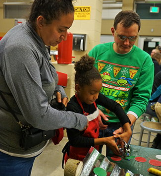 Teacher helps a mom and daughter at makerspace night