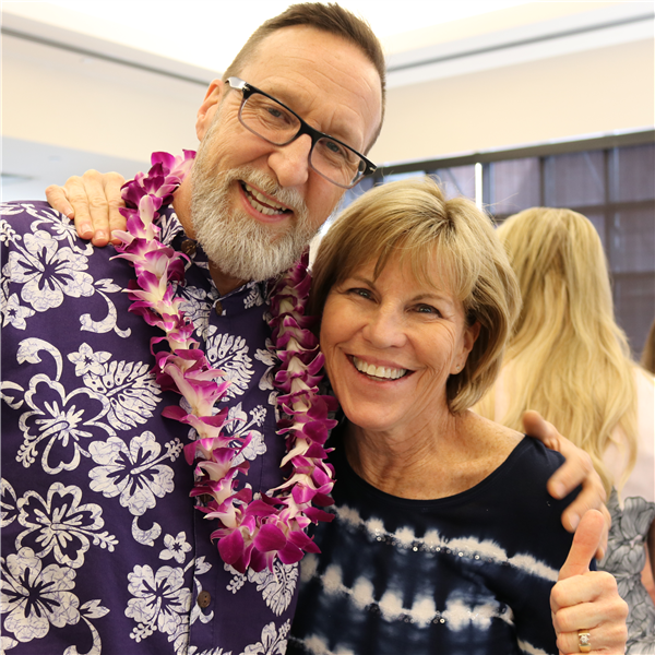 retiree with school principal wearing a hawaiian flower