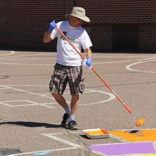Volunteer paints the sidewalk at Sherrelwood Elementary