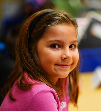 a girl student smiles at the camera at Sherrelwood Elementary