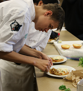 WHS culinary student polishes a dish for presentation