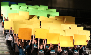 students holding up green and yellow signs