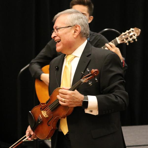 Dr. Lorenzo A. Trujillo holds a violin