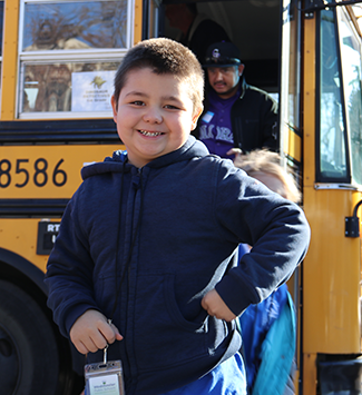 wps student smiles outside a bus