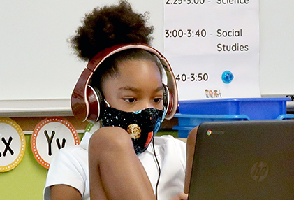 girl student learning on a Chromebook