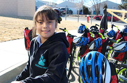 Hodgkins Leadership Academy student smiles with her new bike
