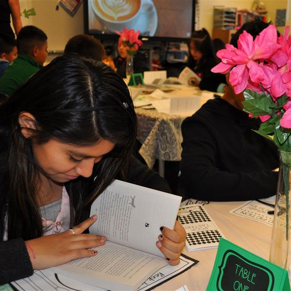 girl reading a book at the book tasting event