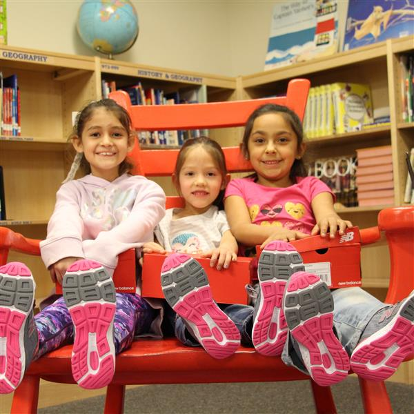 three girls show off their brand new pink and grey shoes