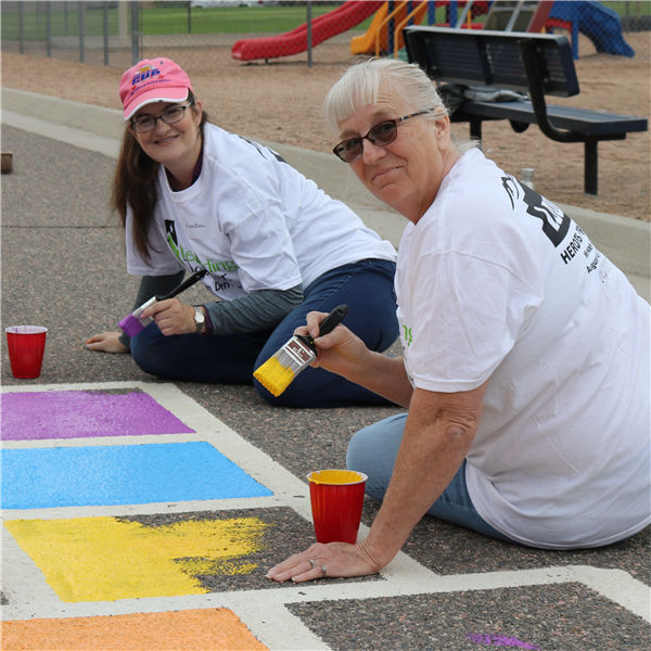 two volunteers painting the playground