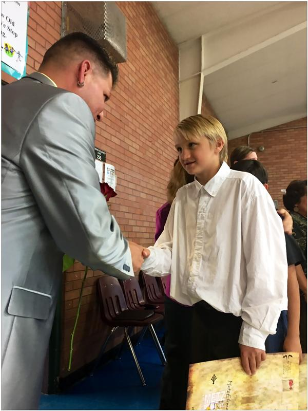 student shaking hands with school leader