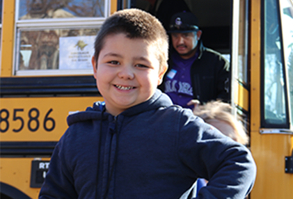 wps student smiling outside a school bus