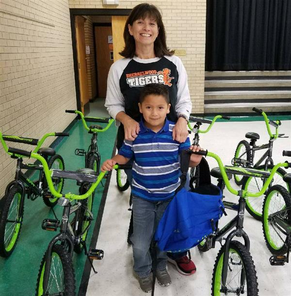 student with teacher standing next to bikes
