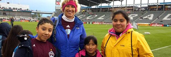 Photo of teacher Ms. Schmitz with students at a Colorado Rapids game.