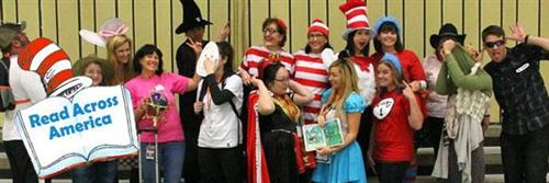 teachers pose dressed like Cat in the Hat for Read Across America Day
