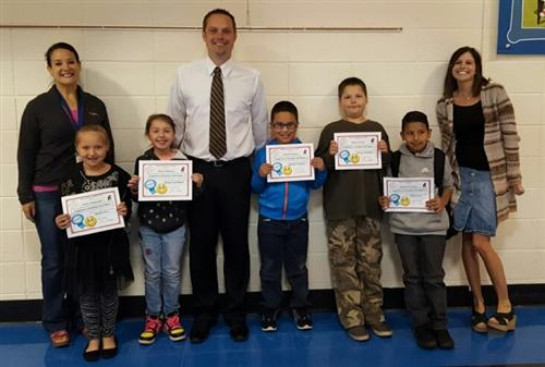 students with their awards showing competency in math and literacy.