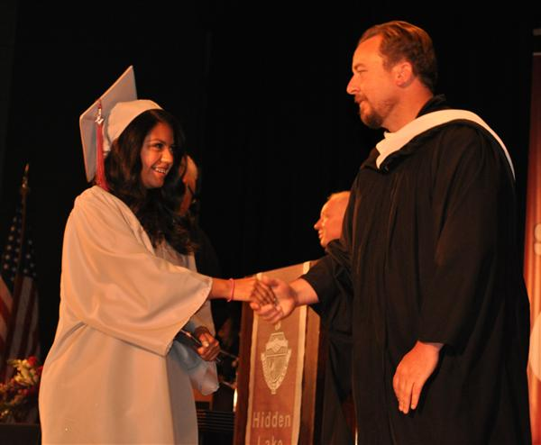 HLHS graduating senior shakes hands with board member Ryan McCoy