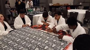 Students working at FBLA convention making blankets for Children's Hospital