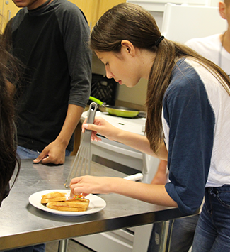 A girl student works on the display of her grilled cheese sandwich
