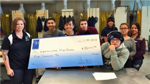 WHS metals students pose with a check to support the program.