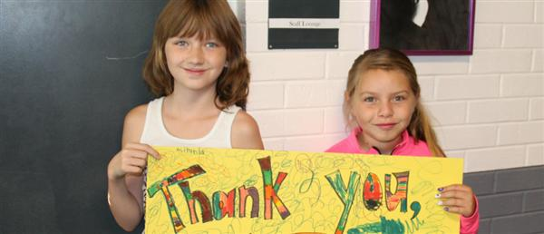 two girls holding a sign that says Thank You