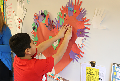 student places the finishes touches on a red heart poster