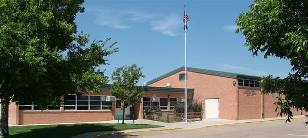 picture of the front of a school with a flag pole and trees outside