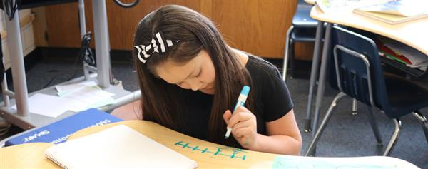 girl wearing a bow working on a math problem
