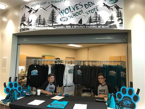 two boys selling tshirts in the wolves den school store