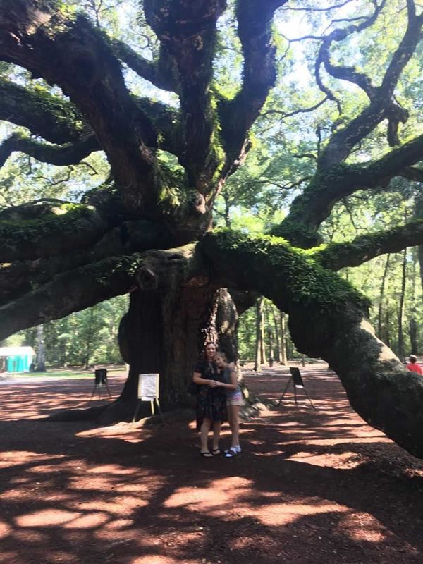 A picture of Ms. Sullivan and her daughter standing under a large oak tree.