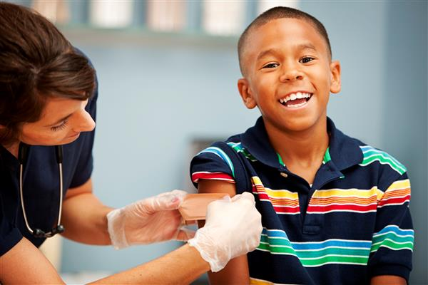 boy smiling after getting a shot from the nurse