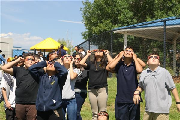 group of students wearing glasses and looking at the eclipse