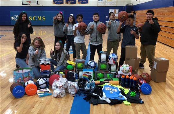 Students holding thumbs up with donations placed in front of them