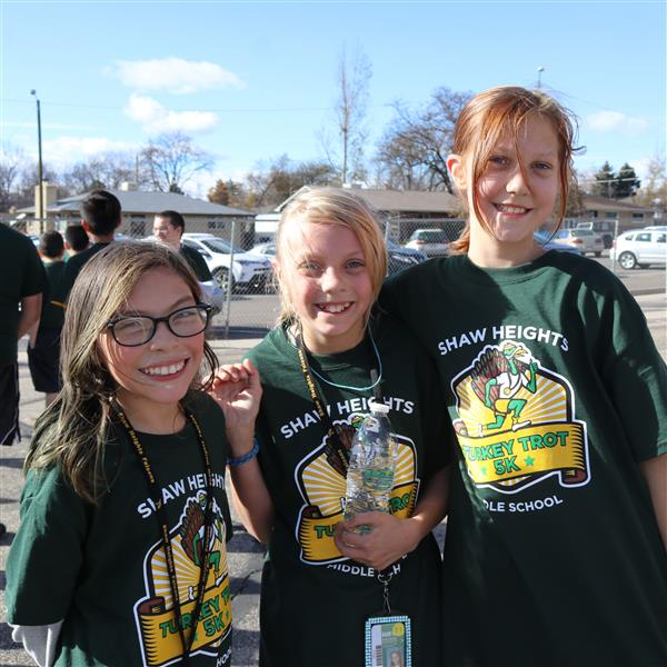 three shaw heights middle school girls pose for a photo after the turkey trot race