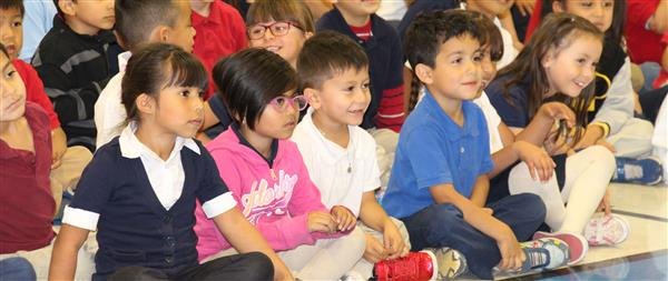kids at an assembly smiling