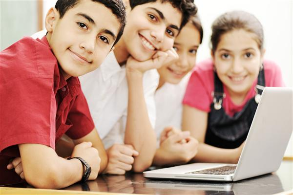 Four students sitting at a computer.