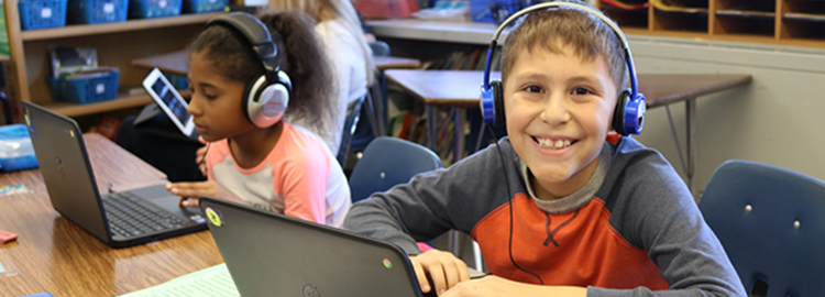 boy student smiles at camera while on the computer