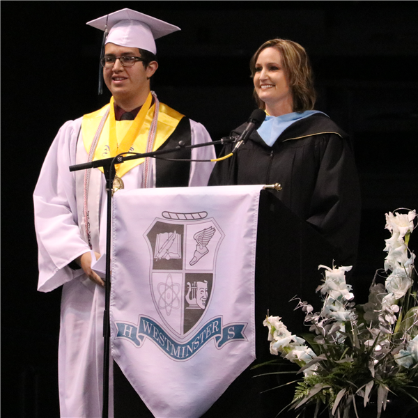 student wearing cap and gown standing next to principal kiffany kiewiet