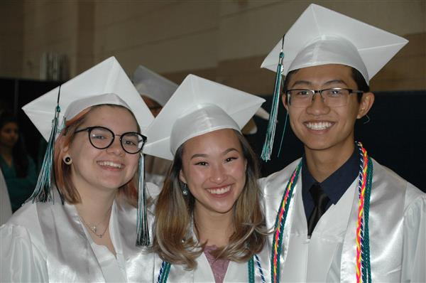 three graduates smiling