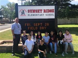 group of students and principal in front of school sign