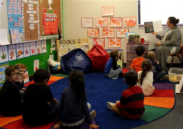 students reading a book in the preschool room