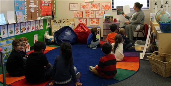 group of students reading a book during circle time