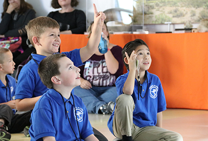Three boy students raise their hand for a question at the museum
