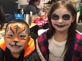two students, one with tiger face painting and the other with skull face painting